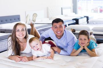 Family choosing mattress in store
