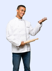 Young afro american chef man extending hands to the side for inviting to come on isolated background