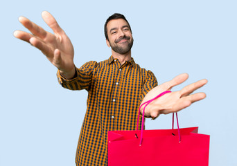 Man with shopping bags presenting and inviting to come with hand on isolated blue background