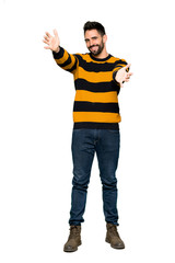 Full-length shot of Handsome man with striped sweater presenting and inviting to come with hand on isolated white background