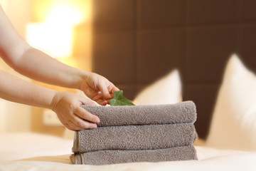 Towels the color of coffee with milk lay on the bed, decorated in the bedroom