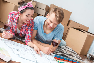 Young couple moving to new place lying drinking wine pointing at plan discussing ideas happy