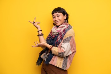 Young hippie woman over yellow wall extending hands to the side for inviting to come