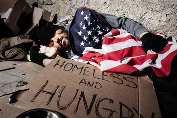 Homeless man sleeping outsie under American flag