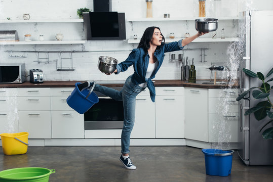 Full length view of shoked woman in jeans dealing with water leak in kitchen