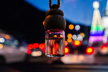 Air freshener for the car hanging at night, red lights and oranges in the background.