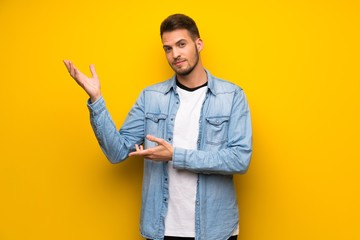 Handsome man over yellow wall extending hands to the side for inviting to come