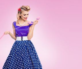 Smiling woman with phone, dressed in pinup style