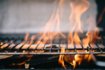 Poster Firewood texture burning firewood with flame through bbq grill grates