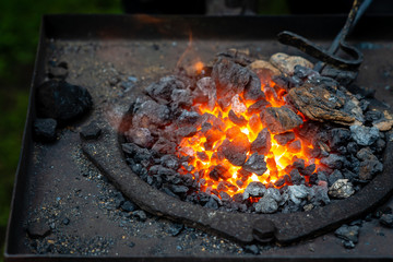 Hot item is inserted into the blacksmith's forge from which the tongues of flame. Concept: blacksmithing, forge - Image