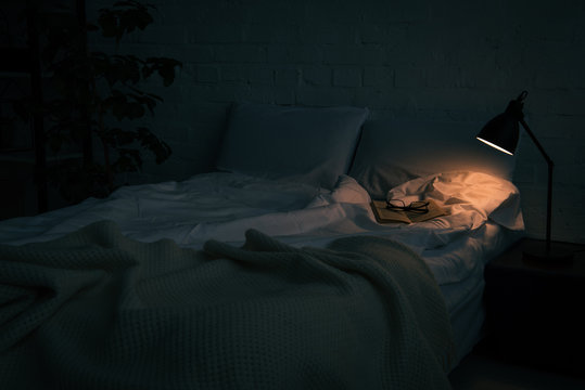 book and glasses on empty bed, plant and lamp on black nightstand at night