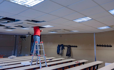 Worker repairing board ceiling with gypsum. In the classroom