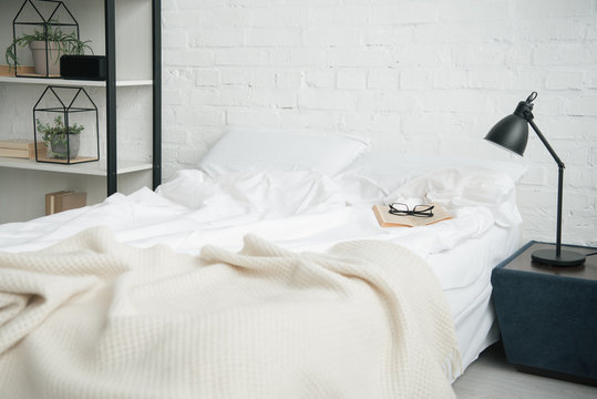 Bedroom with rack, white bed and lamp on nightstand