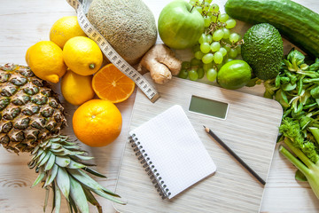 Flat lay composition with scales, healthy vegetables and fruit on wooden background. Weight loss...