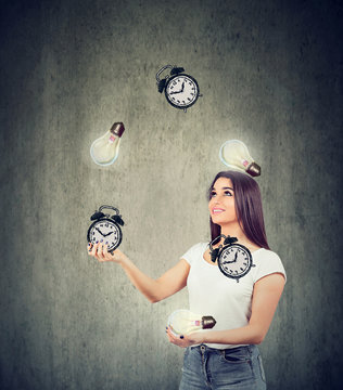 Happy young woman juggling bright lightbulbs and alarm clocks