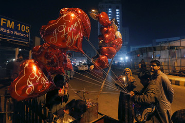 Imran ties as his wife inflates heart shaped balloons for a customer on Valentine's Day from their cart along a road in Karachi