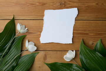gift with flowers on a wooden background, there is free space for text, flat lay