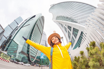 Happy young asian woman traveler tourist in modern business center metropolis among high skyscrapers buildings
