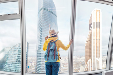 Cheerful young tourist girl at the observation point in modern skyscraper building