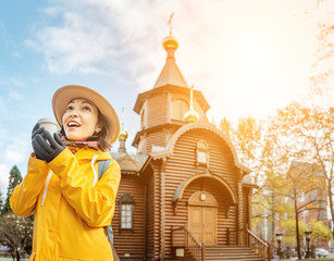Happy tourist girl with hot drink travels in Russia and posing at the background of a old wooden church in authentic russian architecture