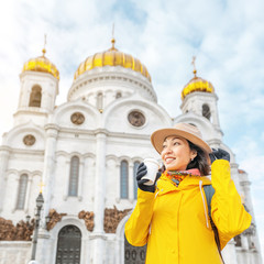 Happy asian tourist woman at the Cathedral of Christ the Savior. Travel and tourism in Russia and Moscow concept. Religion and faith