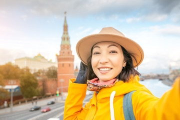 Happy asian woman tourist taking selfie photo on the background of the Kremlin wall tower from the Moscow river embankment. Travel in Russia concept