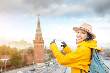 Happy asian woman tourist taking photo by smartphone on the background of the Kremlin wall tower from the Moscow river embankment. Travel in Russia concept