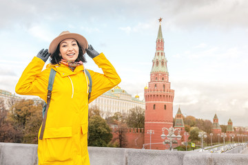 Happy asian woman tourist on the background of the Kremlin wall tower from the Moscow river embankment. Travel in Russia concept