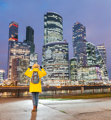 Young happy tourist woman enjoying evening view of the illuminated tall skyscrapers in Moscow city