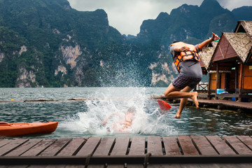 Young man jumping into the lake from the jetty.  Activity relaxing and Adventure trips on summer holidays. relax your way concept. Fototapete