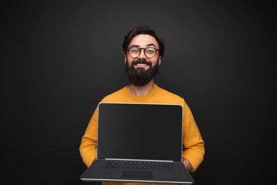 Glad man showing modern laptop