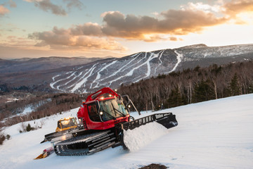A fleet of snowcats grooming Spruce Peak at dusk with Mt. Mansfield in the background, Stowe, Vermont, USA Wall mural