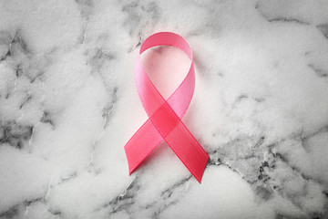 Pink ribbon on marble background, top view. Breast cancer awareness concept