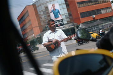 Gabriel, Venezuelan, plays a cuatro of Venezuela as he asks for money on a street of Cucuta