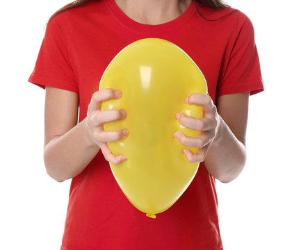Woman squeezing yellow balloon on white background, closeup