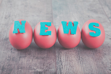 """Four eggs with """"news"""" word on wooden background"""