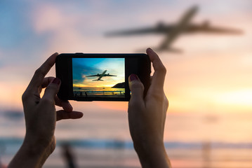 Silhouette of female to take the photo the landscape of sunset with Plane viewpoints in Phuket at Nai Yang Beach, Phuket Province, Thailand.