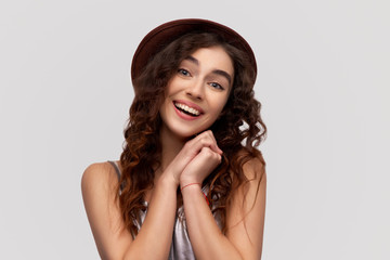 Beautiful young joyful woman keeps hands together, has brown eyes full of happiness, stands against white background, recieves nice gift