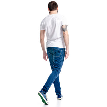 Man in white t-shirt and jeans goes walking on white background isolation, back view