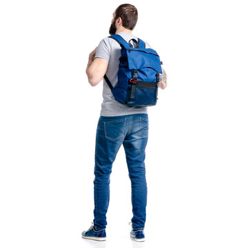 A man tourist in jeans with blue backpack standing looking on white background isolation, back view