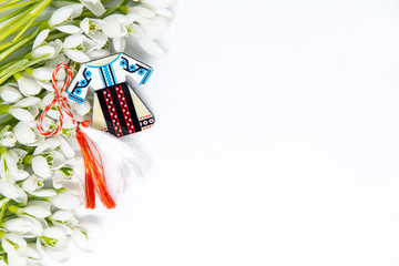 snow drops and pendant known as martisor on white with copy space, balkanic symbol of spring offered to loved ones as a talisman of good luck, health, friendship, love and respect