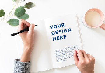 Person Writing in a Blank Notebook Mockup