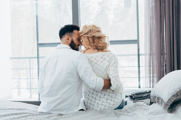 Romantic couple embracing while sitting on bed
