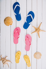 top view of yellow, blue and pink flip flops on white wooden background with seashells