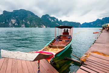 Long-tailed boat floating on the Asia lake and homestay in the among the islands with mountains in background in Thailand