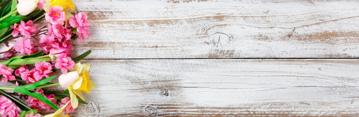 Springtime flowers on white rustic wooden background for seasonal holidays like Easter and Mothers Day