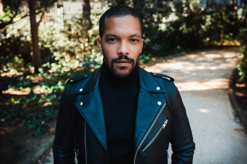 Confident stylish african american man wearing black leather jacket outdoor. Street wear fashion black man.