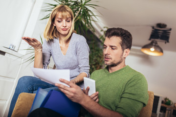 Photo of a positive young couple embracing and calculating the bills at home.