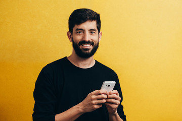 Portrait of young using mobile phone isolated over yellow background