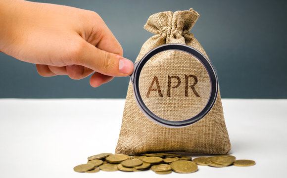 A hand points to a money bag with the word Apr. This is a financial fee, expressed as an annual rate. Applicable to loan, mortgage, credit card. Commercial money investment. APR. Percentage Rate